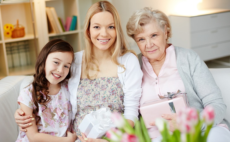 Portrait of happy little girl, her mother and grandmother with giftboxes looking at camera at home
